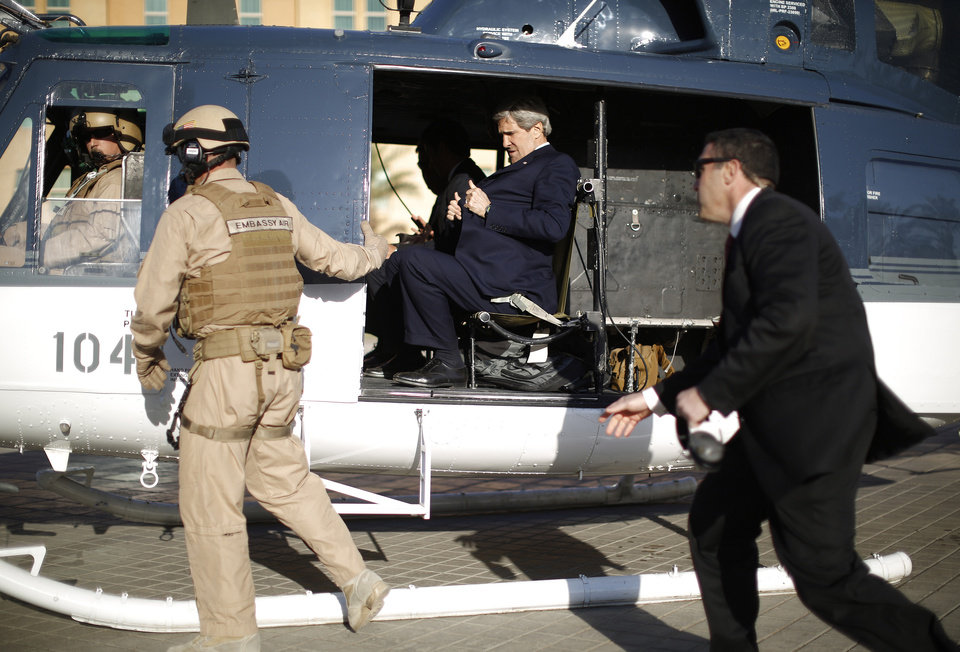 Photo - U.S. Secretary of State John Kerry straps himself into a helicopter as he prepares to fly out of the U.S. Embassy in Baghdad Sunday, March 24, 2013. Kerry was in Iraq today, meeting with officials in an unannounced visit. He says he made it clear in talks with the Iraqi Prime Minister Nouri al-Maliki that the U.S. is unhappy with Iraq for letting Iran use its airspace to ship weapons and fighters to Syria. (AP Photo/Jason Reed, Pool)