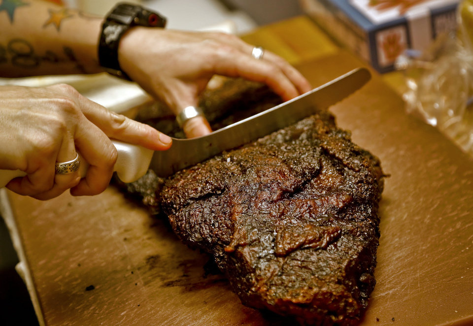 Photo - Chef and partner of the new Back Door Barbecue, Kathryn Mathis, cuts up a brisket in the kitchen at the restaurant at 315 NW 23 in Oklahoma City. Photo by Chris Landsberger, The Oklahoman  CHRIS LANDSBERGER