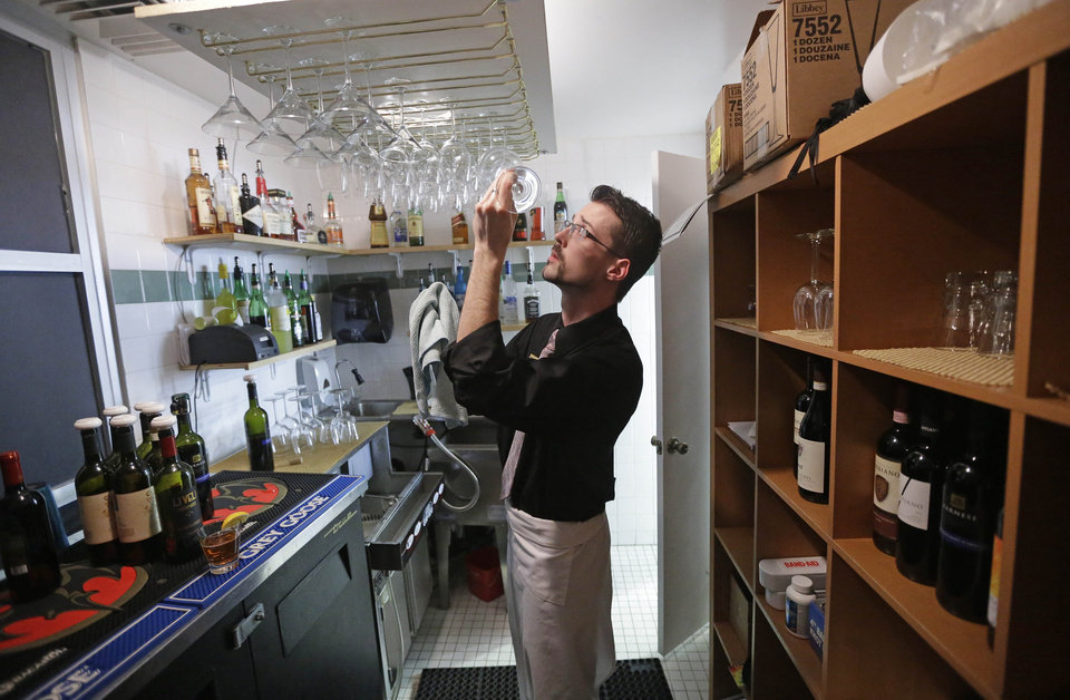 "Photo - Manager Dustin Humes inspects a wine glass in a small room which is out of the view of patrons at Vivace Restaurant Monday, Feb. 26, 2013, in Salt Lake City. Utah lawmakers are considering repealing a law that requires restaurants to mix alcoholic drinks out of view from patrons. Commonly known as ""Zion curtains,"" the mandate went into effect for restaurants in 2010 as part of a compromise when lawmakers lifted a mandate for bars to operate as members-only social clubs. The rule does not apply to restaurants that opened before 2010. A House committee is expected to discuss the bill Wednesday. Restaurant owners and tourism officials say the law is unnecessary and hinders tourism. But some lawmakers say that removing the mandate could encourage underage drinking and influence customers to drink too much. (AP Photo/Rick Bowmer)"