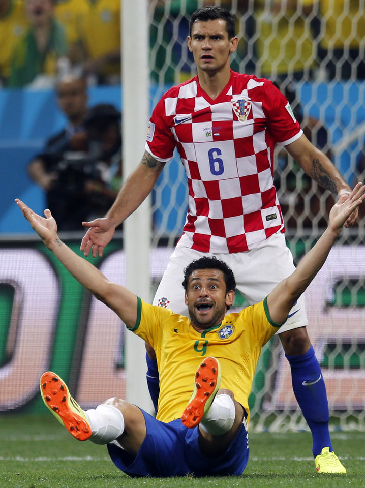 Photo - Brazil's Fred, bottom, raises his arms after a penalty was called against Croatia's Dejan Lovren, top, by referee Yuichi Nishimura, from Japan, during the group A World Cup soccer match between Brazil and Croatia in the opening game of the tournament at the Itaquerao Stadium in Sao Paulo, Brazil, Thursday, June 12, 2014. Brazil was issued a penalty kick following the play leading to a goal by Neymar helping Brazil to a 3-1 victory. (AP Photo/Frank Augstein)