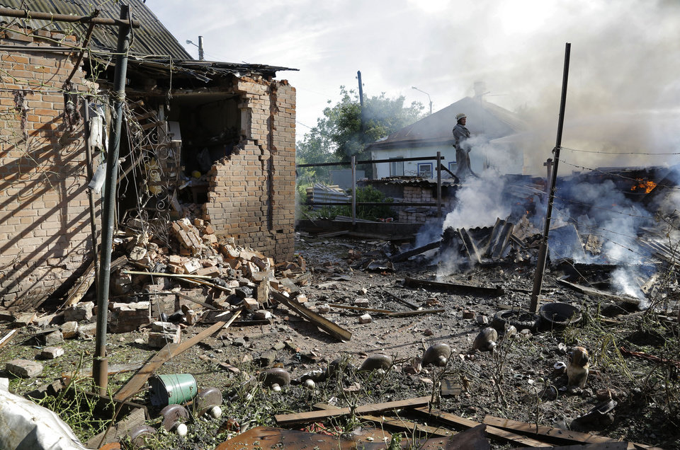 Photo - A fireman tries to extinguish a burning house after shelling in the city of Slovyansk, Donetsk Region, eastern Ukraine Monday, June 30, 2014. Residential areas came under shelling on Monday morning from government forces. (AP Photo/Dmitry Lovetsky)