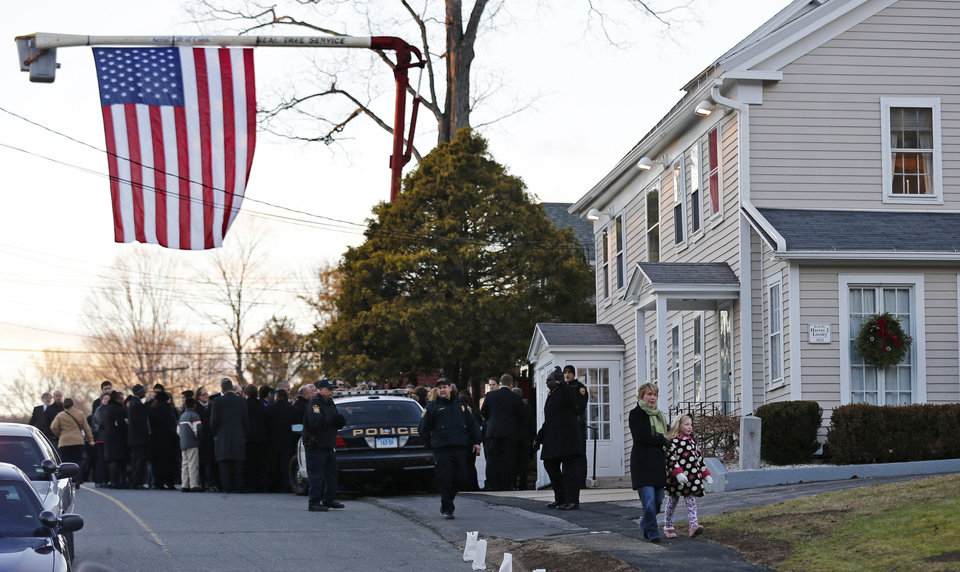 A woman and child walk away from a funeral home after paying their respects at the wake of Sandy Hook Elementary School principal Dawn Lafferty Hochsprung in Woodbury, Conn., Wednesday, Dec. 19, 2012. Hochsprung, was killed when Adam Lanza walked into Sandy Hook Elementary School in Newtown, Conn., Dec. 14, and opened fire, killing 26 people, including 20 children, before killing himself. (AP Photo/Charles Krupa)
