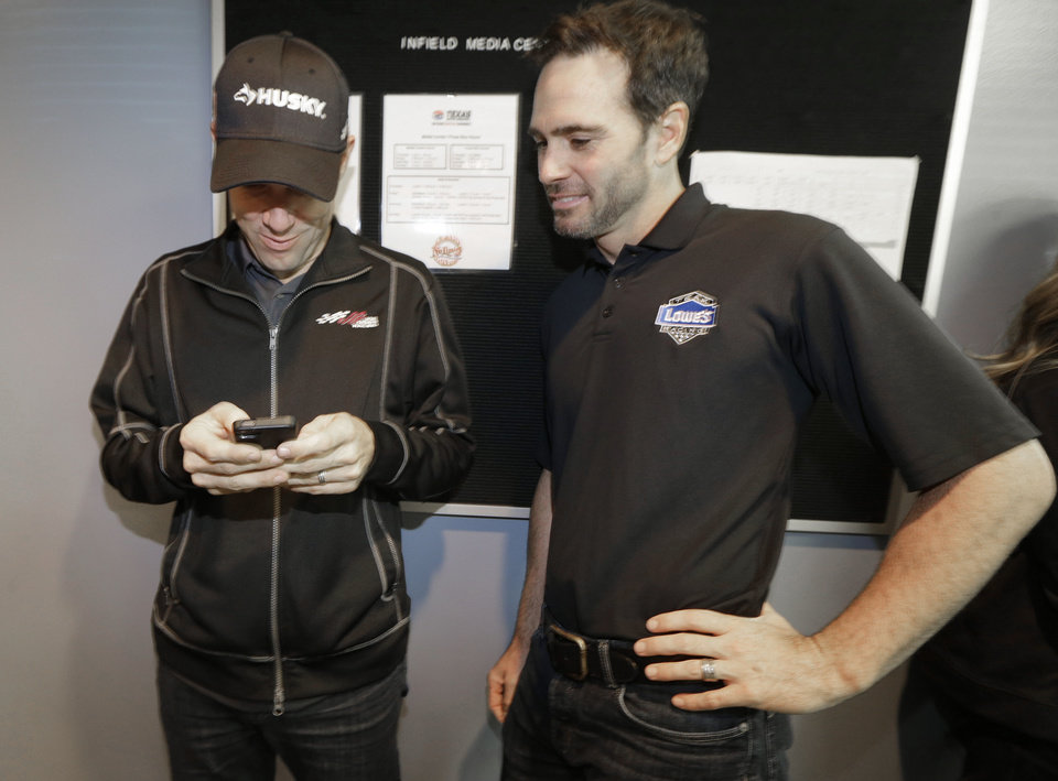 Photo - NASCAR Sprint Cup Series driver Matt Kenseth, left, shows fellow driver Jimmie Johnson something on his smart phone between news conferences in the media center at Texas Motor Speedway in Fort Worth, Texas, Friday, Nov. 1, 2013.  (AP Photo/LM Otero)
