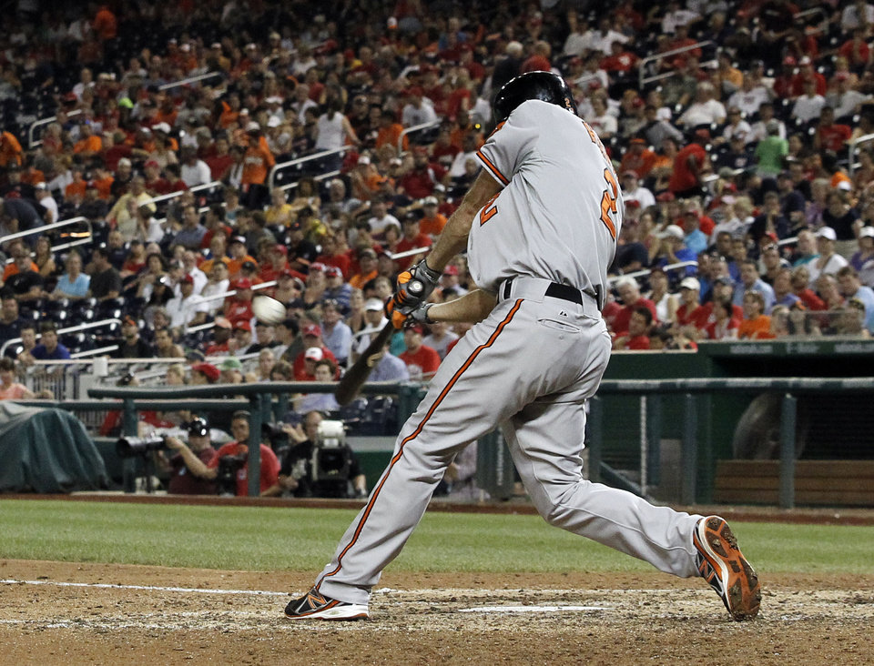 Photo - Baltimore Orioles' J.J. Hardy hits a solo home run during the 11th inning of an interleague baseball game against the Washington Nationals at Nationals Park, Monday, July 7, 2014, in Washington. The Orioles won 8-2, in 11 innings. (AP Photo/Alex Brandon)