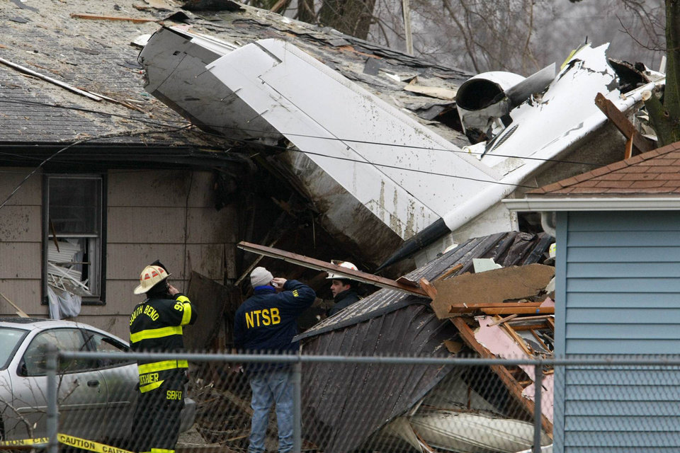 Photo - A National Transportation Safety Board investigator and South Bend firefighters early Monday, March 18, 2013, survey the scene of Sunday's fatal plane crash, along Iowa Street in South Bend, Ind. Photo by James Brosher, South Bend Tribune/AP  James Brosher - AP