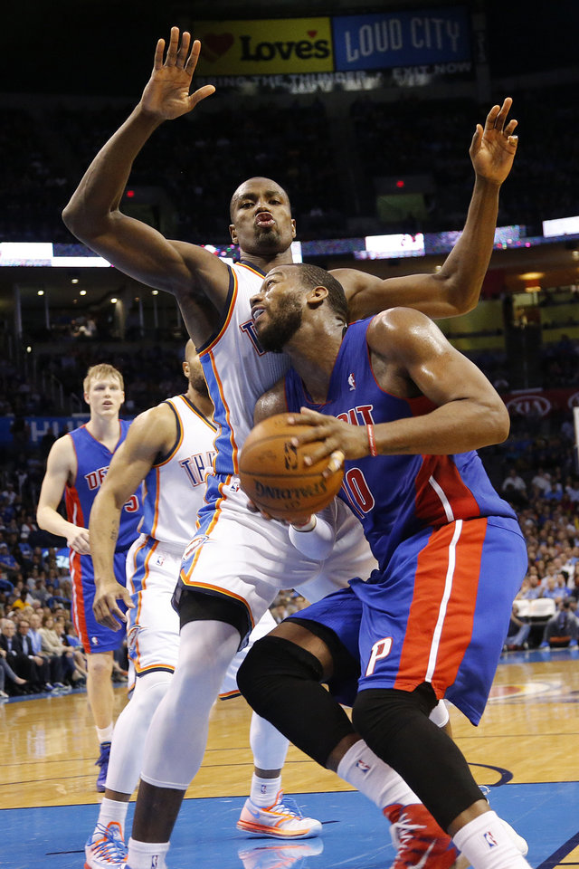 Photo - Oklahoma City's Serge Ibaka (9) defends on Detroit's Greg Monroe (10) during the NBA basketball game between the Oklahoma City Thuder and the Detroit Pistons at Chesapeake Energy Arena in Oklahoma City, Okla. on Wednesday, April 16, 2014.  Photo by Chris Landsberger, The Oklahoman