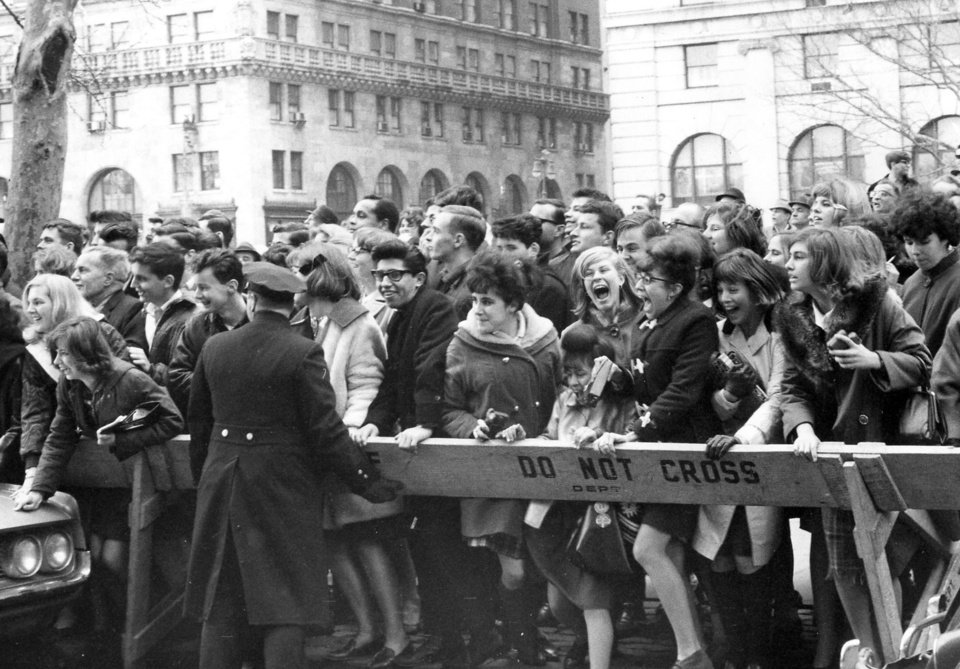 "Photo - FILE - This Feb. 7, 1964 file photo shows fans pushing forward in hopes of getting a view of The Beatles after their arrival for an American tour in New York. Sunday marks the 50th anniversary of The Beatles' performance on ""Ed Sullivan,"" their first appearance in America. Nielsen says 45 percent of all TV sets in use at the time were tuned into the broadcast, with fans and the uninitiated alike gathered shoulder to shoulder in their living rooms. The Beatles landed on a trigger point when they hit America. It was a pop culture sonic boom spurred by talent, timing and luck that's still rattling the windows. (AP Photo, File)"