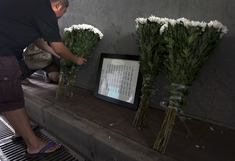 Photo -   A Chinese man places flowers next to a frame with the names of flood's victim under a railway bridge, where a motorist drowned a week ago in Beijing, China Saturday, July 28, 2012. A small group of people laid down white chrysanthemums or lit candles Saturday to pay tribute to those who died in the storm that ravaged Beijing one week ago, killing at least 77. (AP Photo/Andy Wong)