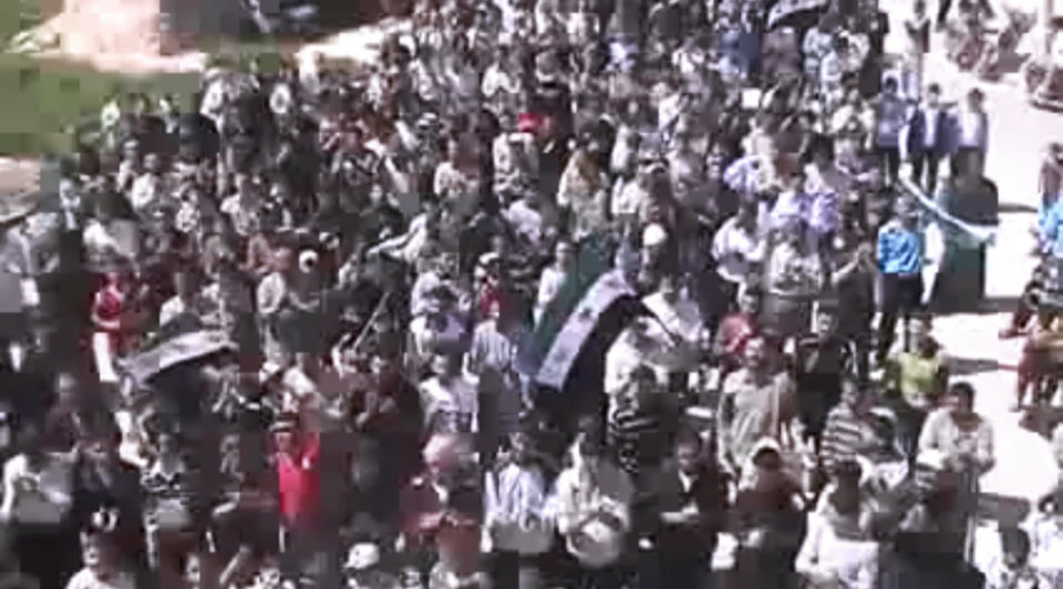 Photo -   This image made from amateur video released by the Shaam News Network and accessed Thursday, April 12, 2012, purports to show Syrians chanting slogans during a demonstration in Idlib, Syria. Syrian forces halted attacks on opposition strongholds Thursday in line with a U.N.-brokered truce but the regime defied demands by international envoy Kofi Annan to pull troops back to their barracks, activists said. (AP Photo/Shaam News Network via AP video) TV OUT, THE ASSOCIATED PRESS CANNOT INDEPENDENTLY VERIFY THE CONTENT, DATE, LOCATION OR AUTHENTICITY OF THIS MATERIAL