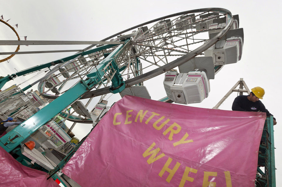 A man places a sign at the Century Wheel ride at the Arkansas State Fairgrounds in Little Rock, Ark., Thursday, Oct. 11, 2012. The fair is scheduled to open Friday, Oct. 12, and run through Oct. 21. (AP Photo/Danny Johnston)