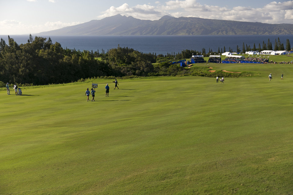 Photo - With Molokai Island in the distance, Matt Kuchar and Jordan Spieth make their way down the 18th fairway during the third round of the Tournament of Champions golf tournament, Sunday, Jan. 5, 2014, in Kapalua, Hawaii. (AP Photo/Marco Garcia)