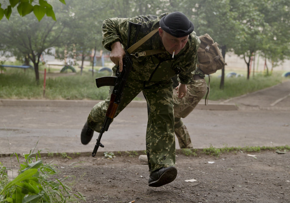 Photo - A pro-Russian rebel runs for cover during clashes with Ukrainian troops on the outskirts of Luhansk, Ukraine, Monday, June 2, 2014. Hundreds of pro-Russia insurgents attacked a border guard base in eastern Ukraine on Monday, with some firing rocket-propelled grenades from the roof of a nearby residential building. At least five rebels were killed when the guards returned fire, a spokesman for the border guard service said.(AP Photo/Vadim Ghirda)