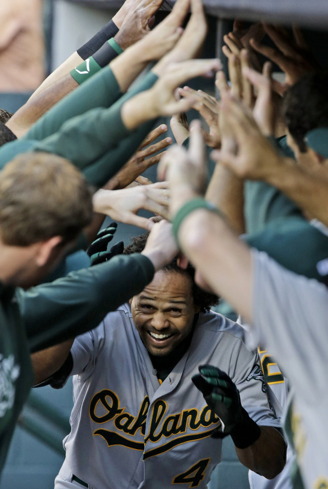 Oakland Athletics\' Coco Crisp is welcomed back to the dugout after hitting a solo home run to start the baseball game against the Houston Astros, Friday, April 5, 2013, in Houston. (AP Photo/Pat Sullivan)