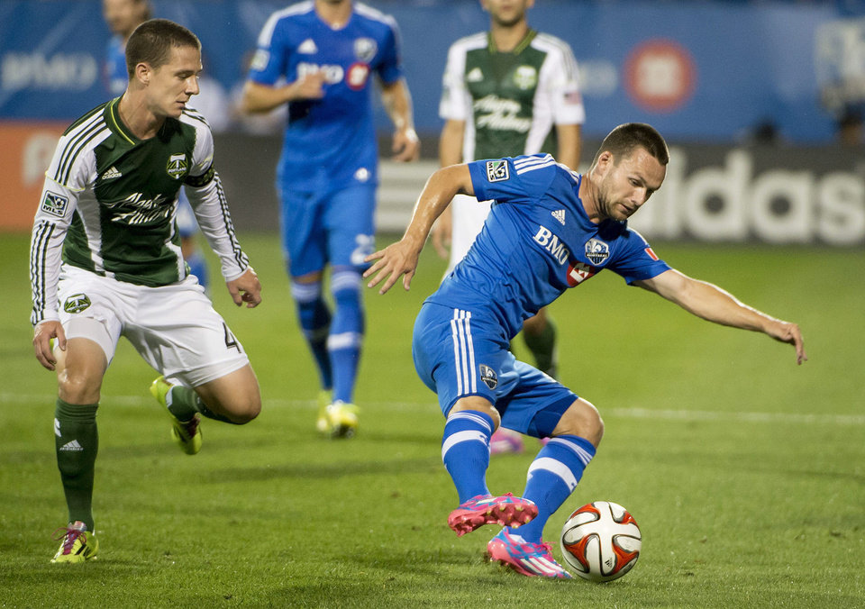 Photo - Montreal Impact's Jack McInerney, right, evades Portland Timbers' Will Johnson during the first half of an MLS soccer game Sunday, July 27, 2014, in Montreal. (AP Photo/The Canadian Press, Peter McCabe)