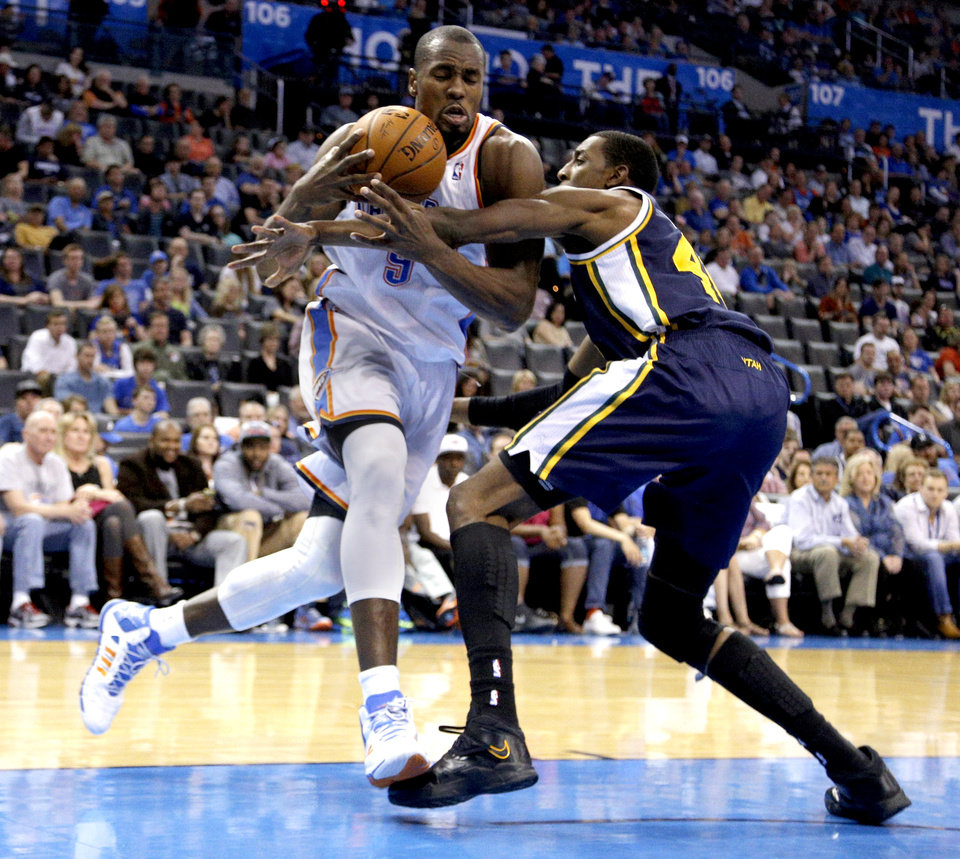 Oklahoma City 's Serge Ibaka (9) derives past Utah's Jeremy Evans (40) during the NBA game between the Oklahoma City Thunder and the Utah Jazz at the Chesapeake Energy Arena, Sunday, March 30, 2014, in Oklahoma City. Photo by Sarah Phipps, The Oklahoman