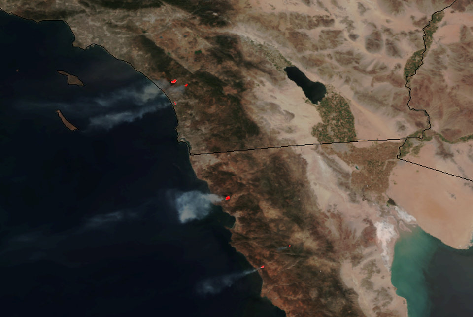 Photo - This May 14, 2014 image provided by NASA shows numerous large wildfires burning across sections of northern Baja and southern California, producing plumes of moderate to dense smoke and combining with blowing dust and sand moving west off the coast and well into the Pacific Ocean. Nine fires in all were burning an area of more than 14 square miles amid a heat wave and dry conditions, said San Diego County officials, who warned also of poor air quality with black and gray smoke wafting over the region. (AP Photo/NASA)