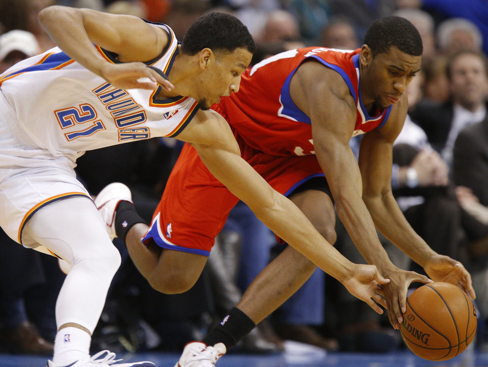 Photo - Oklahoma City's Andre Roberson (21) and Philadelphia's Hollis Thompson (31) go for a loose ball during an NBA basketball game between the Oklahoma City Thunder and the Philadelphia 76ers at Chesapeake Energy Arena in Oklahoma City, Tuesday, March 4, 2014. Oklahoma City won 125-92.  Photo by Bryan Terry, The Oklahoman