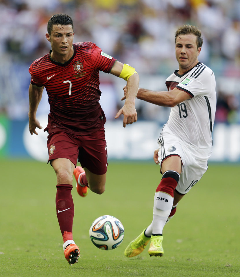 Photo - Portugal's Cristiano Ronaldo (7) races past Germany's Mario Goetze (19) during the group G World Cup soccer match between Germany and Portugal at the Arena Fonte Nova in Salvador, Brazil, Monday, June 16, 2014.  (AP Photo/Natacha Pisarenko)
