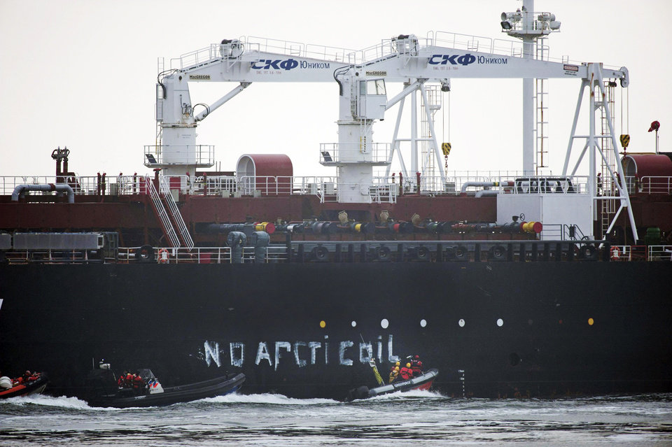 Photo - This image made available by environmental organization Greenpeace  shows Greenpeace activists aboard inflatable boats paint 'No Arctic Oil' on the side of the Mikhail Ulyanov oil tanker in Rotterdam, Netherlands, on Thursday, May 1, 2014. Greenpeace International activists are attempting to prevent a Russian tanker carrying the first oil from a new offshore platform in the Arctic from mooring at Rotterdam Port. The environmental group said Thursday it has sent two ships, Rainbow Warrior III and Esperanza, plus rubber rafts, paragliders and activists on shore, to meet the Mikhail Ulyanov, a tanker chartered by Russia's state-controlled oil company, Gazprom OAO. (AP Photo/Marten van Dijl, Greenpeace) NO SALES, NO ARCHIVE