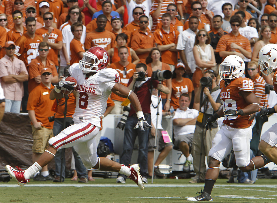 Photo - Texas fans look on as Oklahoma's Dominique Whaley (8) runs to the end zone for a touchdown during the Red River Rivalry college football game between the University of Oklahoma Sooners (OU) and the University of Texas Longhorns (UT) at the Cotton Bowl in Dallas, Saturday, Oct. 8, 2011. Photo by Chris Landsberger, The Oklahoman