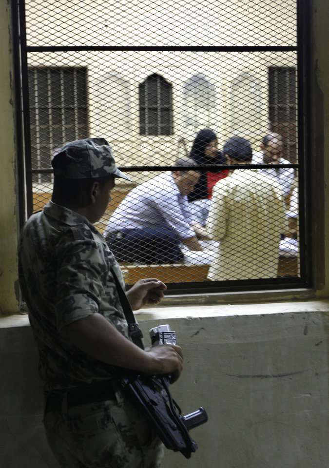 Photo -   An Egyptian soldier watches elections officials as they count ballots at a polling center during the second day of the presidential runoff, in Cairo, Egypt, Sunday, June 17, 2012. Egyptians are choosing between a conservative Islamist and Hosni Mubarak's ex-prime minister in a second day of a presidential runoff that has been overshadowed by the domination of the country's military. (AP Photo/Amr Nabil)
