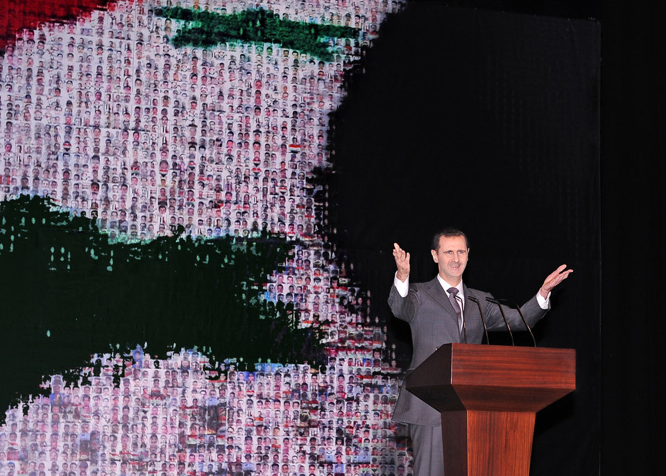 Photo - In this photo released by the Syrian official news agency SANA, Syrian President Bashar Assad speaks at the Opera House in central Damascus, Syria, Sunday, Jan. 6, 2013. Syrian President Bashar Assad on Sunday outlined a new peace initiative that includes a national reconciliation conference and a new government and constitution but demanded regional and Western countries stop funding and arming rebels first.(AP Photo/SANA)