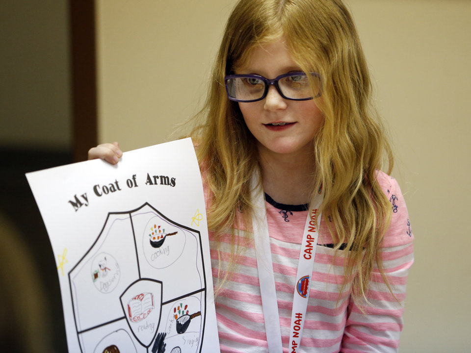 Photo -  Casey Graves shares her self-made Coat of Arms as kids attend Camp Noah on Thursday in Moore. Photo by Steve Sisney, The Oklahoman   STEVE SISNEY -  THE OKLAHOMAN