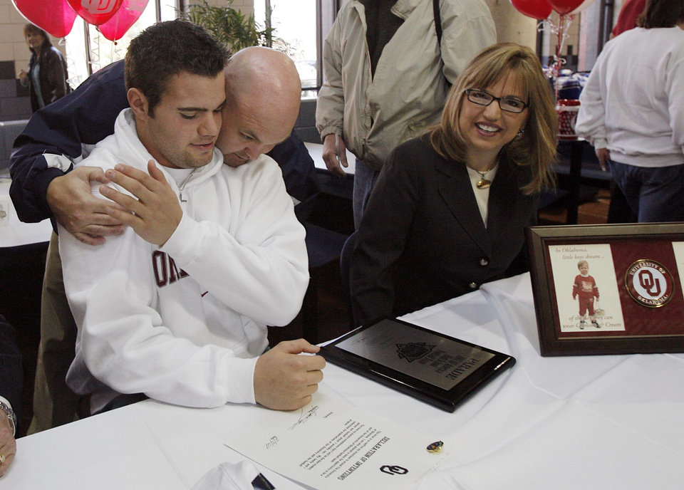 Enid's Austin Box gets a hug from Plainsmen defensive coordinator Tommy Parker as his mother Gail looks on after Box signed his letter of intent to play football with the University of Oklahoma on Wednesday, Feb. 7, 2007, in Enid, Okla.     by Chris Landsberger, The Oklahoman