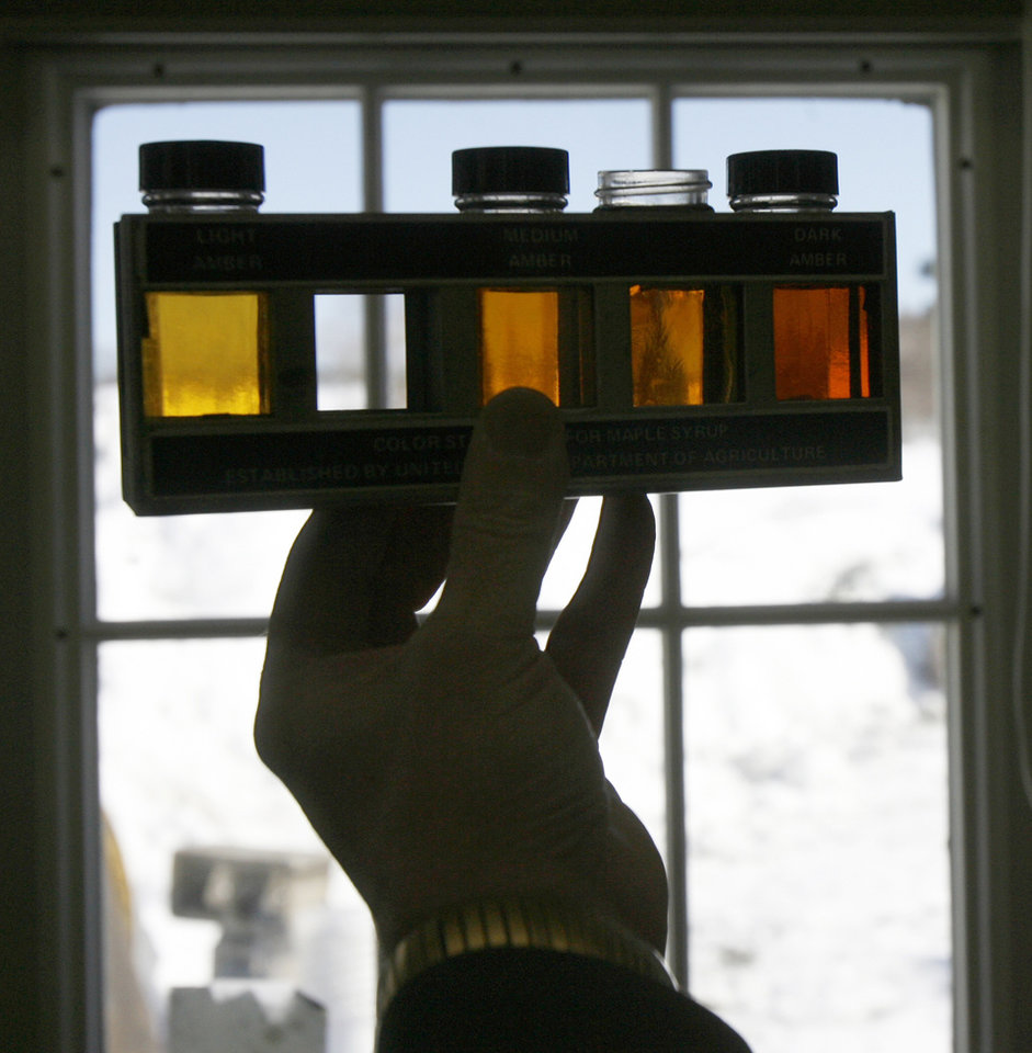 "Photo -   FILE-In this March 17, 2008, file photo, Henry Marckres holds a maple sample up for viewing in East Montpelier, Vt. Vermonters have grown accustomed to their ""fancy"" ""amber"" and ""grade B"" types of maple syrup but new consumers may not be so sweet on the terms. So the country's largest producer of the pancake topping is thinking of doing away with those terms and adopting new international names with flavor descriptions to help consumers delineate between four different colored and flavored syrups and to match new worldwide terms. The four classifications would be golden color, delicate taste; amber color, rich taste; dark color, robust taste; and very dark color, strong taste. (AP Photo/Toby Talbot)"