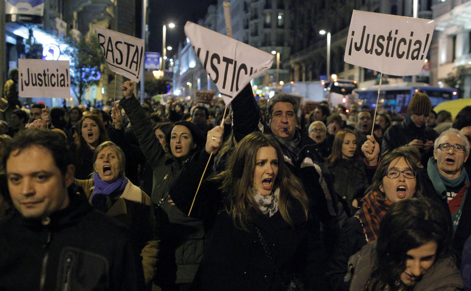 Protestors shout slogans as they carry a banner reading, 'Justice' during a demonstration against corruption, in Madrid, Friday, Feb. 1, 2013. Spain's top prosecutor says there is sufficient cause to investigate fresh allegations of irregular financing of Spain's governing Popular Party and that if necessary Prime Minister Mariano Rajoy would be called in for questioning. (AP Photo/Andres Kudacki)