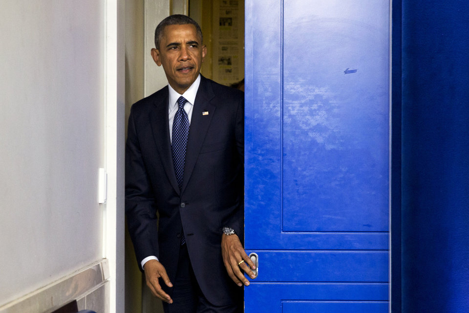 Photo - President Barack Obama enters the briefing room to speak about foreign policy and escalating sanctions against Russia in response to the crisis in Ukraine in the James Brady Press Briefing Room at the White House in Washington, Wednesday, July 16, 2014.  (AP Photo/Jacquelyn Martin)