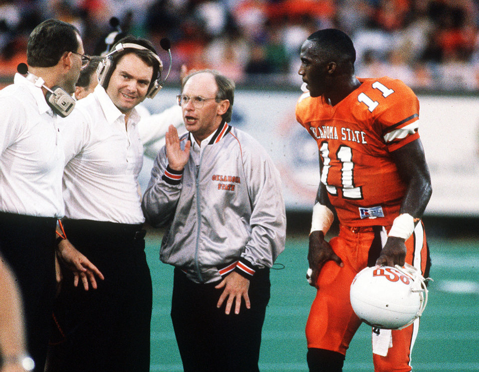 OKLAHOMA STATE UNIVERSITY / COWBOYS FOOTBALL: OSU player Hart Lee Dykes listens to coaches Pat Jones, right, Houston Nutt, middle, and unidentified.