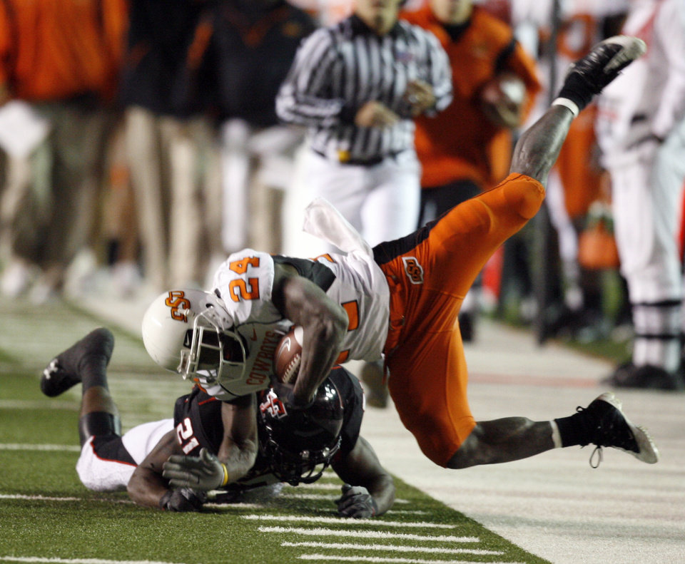 Photo - Kendall Hunter carries and is tackled by L.A. Reed during the first half of the college football game between the Oklahoma State University Cowboys (OSU) and the Texas Tech Red Raiders at Jones AT&T Stadium on Saturday, Nov. 8, 2008, in Lubbock, Tex.By Steve Sisney/The Oklahoman
