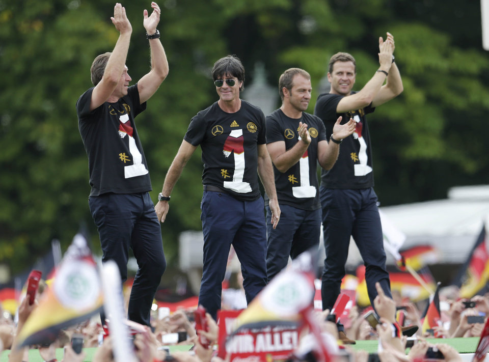 Photo - The German coaching team, from left, goalkeeper coach Andreas Koepke, head coach Joachim Loew, assistant coach Hansi Flick and team manager Oliver Bierhoff wave from the stage after the arrival of the German national soccer team in Berlin Tuesday, July 15, 2014. Germany beat Argentina 1-0 on Sunday to win its fourth World Cup title.  (AP Photo/Petr David Josek)