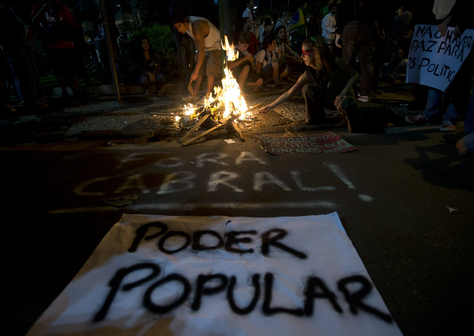 Photo - Demonstrators ignite pieces of wood next to spray-painted messages that read in Portuguese;