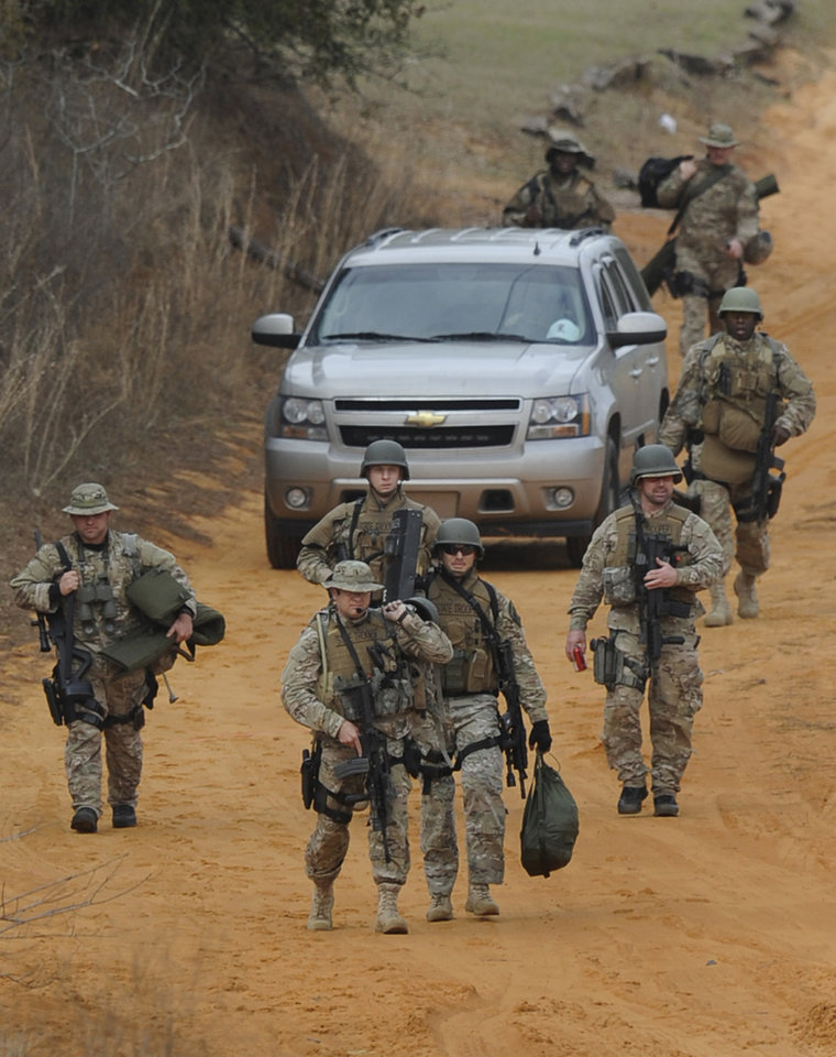 Heavily armed men come back down the hill from the direction of the suspect's home at the Dale County hostage scene near Midland City, Ala. on Wednesday Jan. 30, 2013. Police SWAT teams and hostage negotiators were locked in a standoff Wednesday with a gunman authorities say intercepted a school bus, killed the driver, snatched a 6-year-old boy and retreated into a bunker at his home. (AP Photo/Montgomery Advertiser, Mickey Welsh)    NO SALES