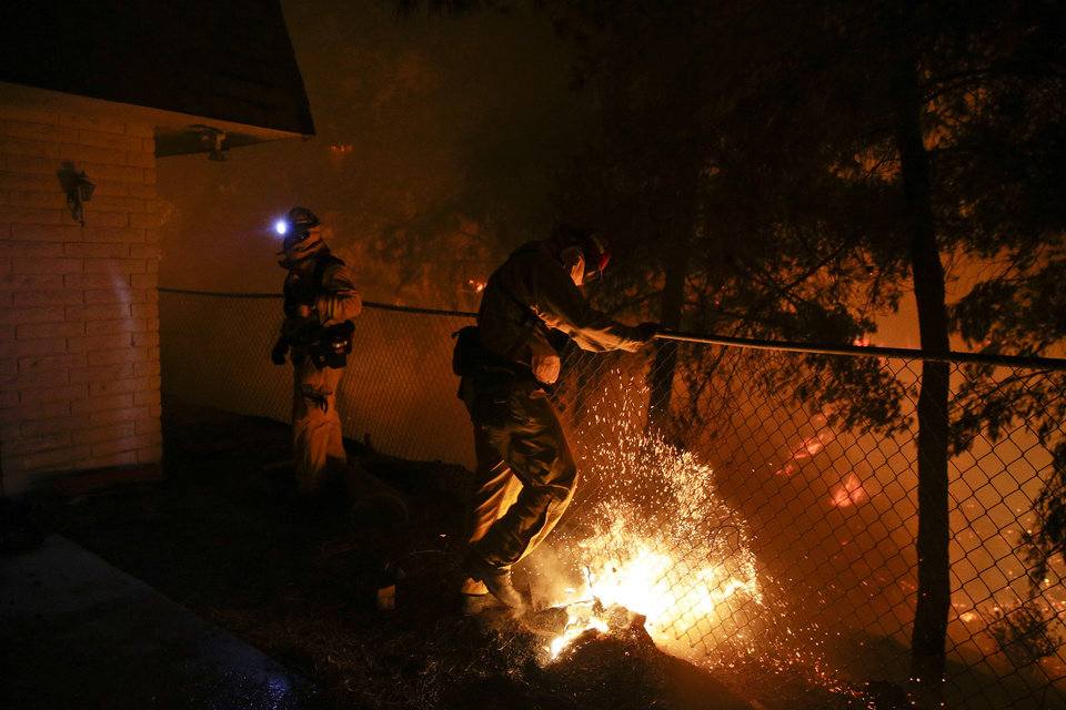 Photo - A firefighter puts out a small spot fire on Wednesday, May 14, 2014, in San Marcos, Calif. Flames engulfed suburban homes and shot up along canyon ridges in one of the worst of several blazes that broke out Wednesday in Southern California during a second day of a sweltering heat wave, taxing fire crews who fear the scattered fires mark only the beginning of a long wildfire season. (AP Photo)