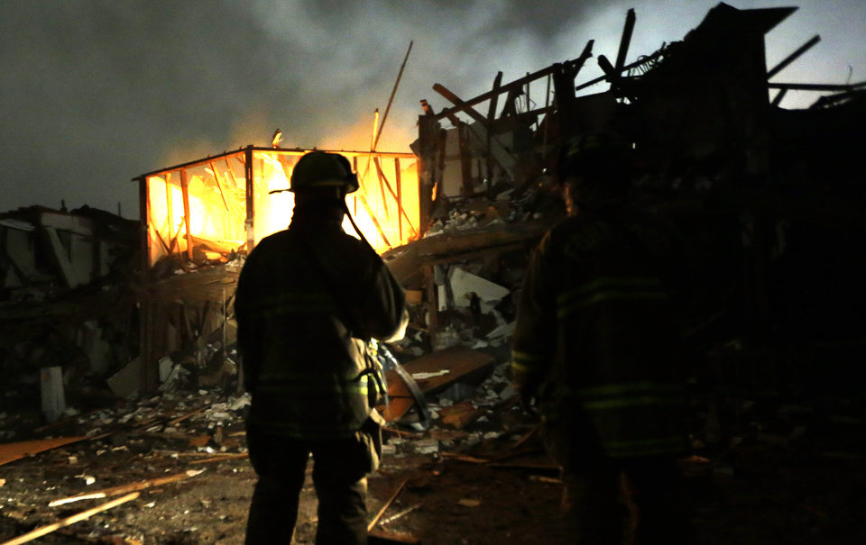 Photo - Firefighters use flashlights early Thursday morning, April 18, 2013 to search a destroyed apartment complex near a fertilizer plant that exploded Wednesday night in West, Texas. The massive explosion killed as many as 15 people and injured more than 160, shaking the ground with the strength of a small earthquake and leveling homes and businesses for blocks in every direction. (AP Photo/LM Otero)