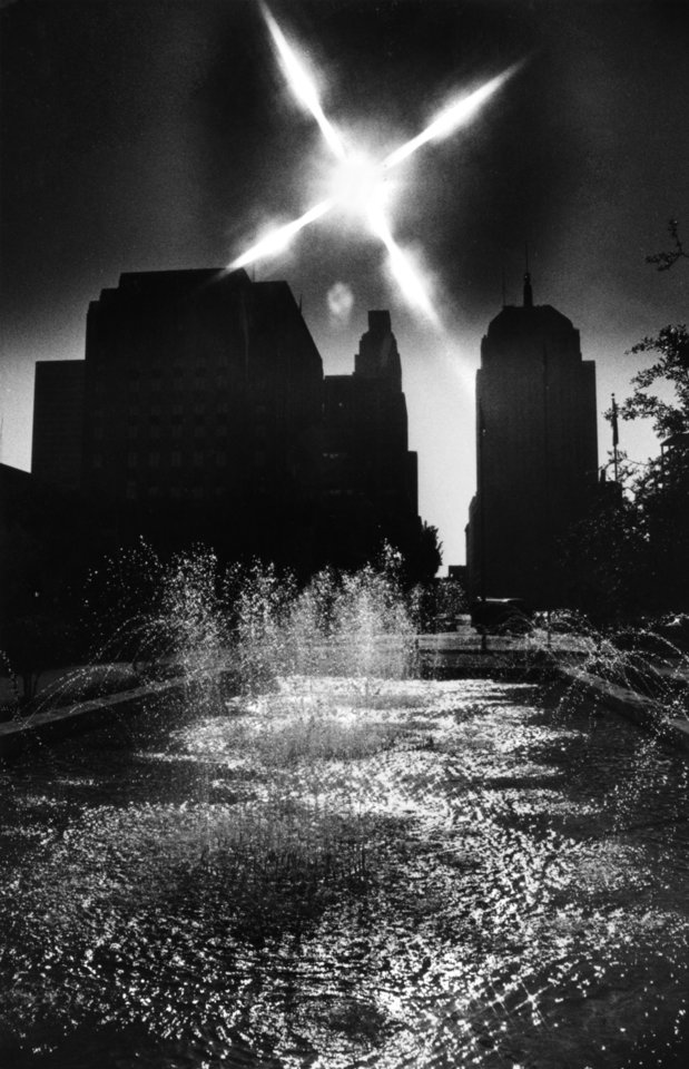 OKLAHOMA CITY / SKY LINE / OKLAHOMA:  Bubbling water glints with light from morning sun beaming from behind buildings in downtown Oklahoma City.  The fountain is in the plaza area on the east side of the Municipal Building.  Staff photo by Roger Klock.  Photo dated 05/06/1980 and published 06/04/1980 in The Oklahoma City Times.