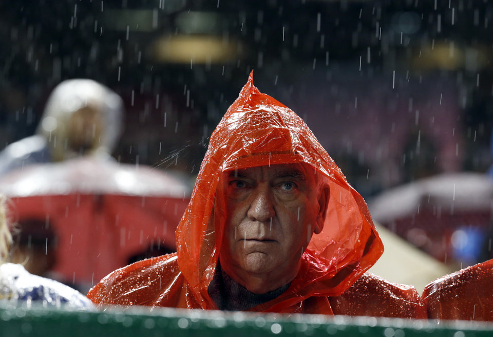 Photo - A fan sits in the rain during the third inning of a baseball game between the Washington Nationals and the Los Angeles Dodgers at Nationals Park, Monday, May 5, 2014, in Washington. (AP Photo/Alex Brandon)