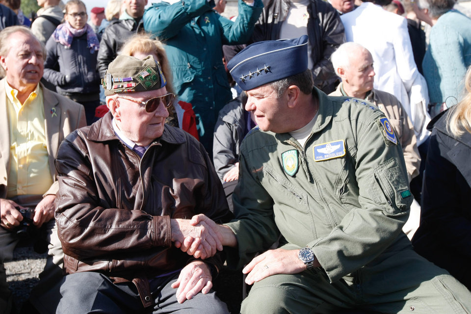 Photo - Gen. Philip M. Breedlove Commander, U.S. Air Forces in Europe, right, shakes hands with U.S WW II veteran 90-year-old Curtis Philipps from Georgia, who landed in Picauville on June 6, 1944, during a ceremony  in homage to the English and American airborne and pilots,  at the Memorial of airborne and US Air Force, in Picauville, France, as part of the commemoration of the 70th D-Day anniversary, Thursday, June 5, 2014. World leaders and veterans prepare to mark the 70th anniversary of the invasion this week in Normandy. (AP Photo/Claude Paris)