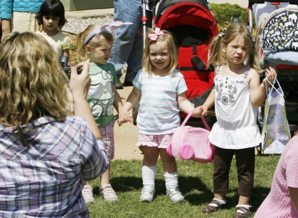 Photo - Lindsey Martin takes a photo of 2-year-olds, from left, Addison Martin, Gaby Alspaugh and Madelyn Conner during an Easter egg hunt and carnival Saturday at Plunkett Park at the University of Central Oklahoma in Edmond. Photo by Paul Hellstern, The Oklahoman  PAUL HELLSTERN