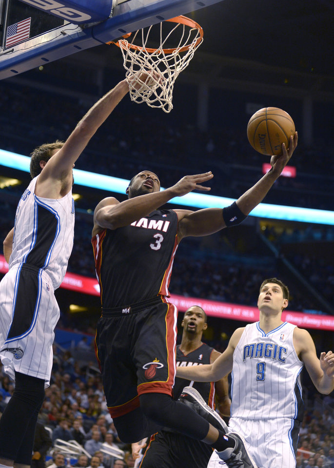 Photo - Miami Heat guard Dwyane Wade (3) goes up for a shot in front of Orlando Magic forward Josh McRoberts, left, as Nikola Vucevic (9) and Chris Bosh, second from right, watch during the first half of an NBA basketball game in Orlando, Fla., Monday, Dec. 31, 2012. (AP Photo/Phelan M. Ebenhack)