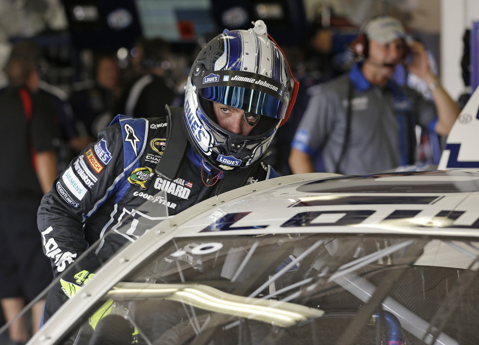 Photo - Jimmie Johnson checks on his car as crew members make adjustments in the garage during practice for the NASCAR Sprint Cup auto race at Daytona International Speedway, Thursday, July 4, 2013, in Daytona Beach, Fla. (AP Photo/John Raoux)