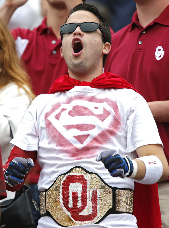 Photo - An Oklahoma fan cheers for the Sooners during the college football game between the University of Oklahoma Sooners (OU) and the University of Texas Longhorns (UT) during the Red River Showdown at the Cotton bowl in Dallas, Texas on Saturday, Oct. 11, 2014. Photo by Chris Landsberger, The Oklahoman