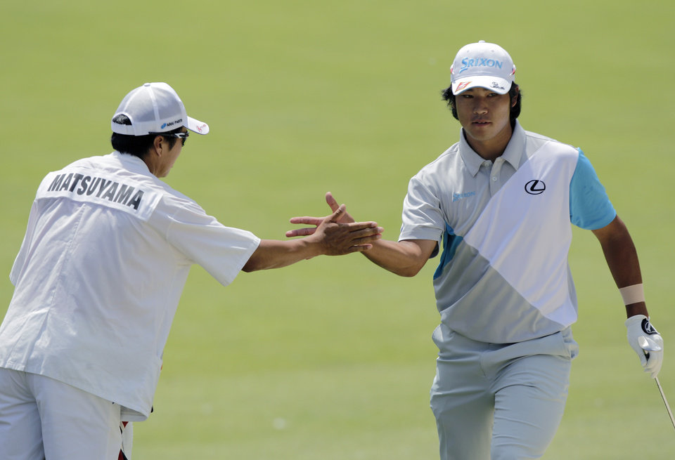 Photo - Hideki Matsuyama, right, of Japan, celebrates with his caddie after holing out from the sand on the second hole during the final round of the Memorial golf tournament, Sunday, June 1, 2014, in Dublin, Ohio. (AP Photo/Jay LaPrete)