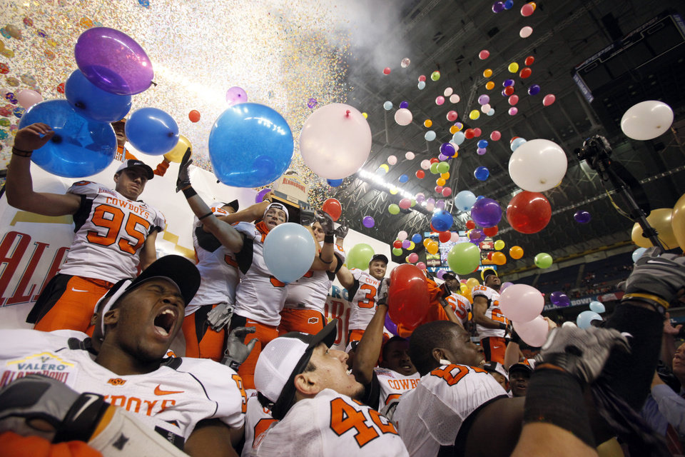 Photo - Oklahoma State celebrates their win over Arizona in the Valero Alamo Bowl  at the Alamodome in San Antonio, Texas, Wednesday, December 29, 2010. OSU won, 36-10. Photo by Sarah Phipps, The Oklahoman