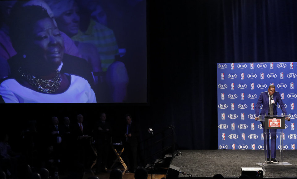 Photo - Wanda Pratt is seen on the screen crying as her son Kevin Durant says thank you to her for being the MVP during a news conference announcing Durant as the winner of the 2013-14 Kia NBA Basketball Most Value Player Award in Oklahoma City, Okla. on Tuesday, May 6, 2014. Photo by Chris Landsberger, The Oklahoman