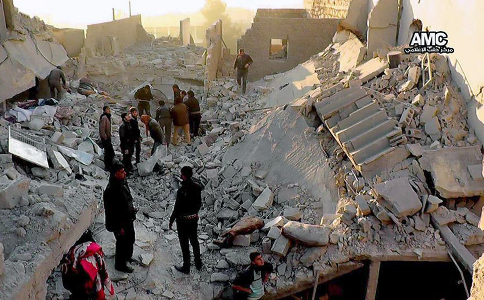 Photo - In this Monday, Jan. 6, 2014 citizen journalism image provided by Aleppo Media Center, AMC, which has been authenticated based on its contents and other AP reporting, Syrians inspect the rubble of destroyed buildings following a Syrian government airstrike in Aleppo, Syria. Syrian rebel groups battled one another Monday for control of a provincial capital, part of a vicious round of score settling targeting an al-Qaida affiliate that gained stature fighting President Bashar Assad but alienated many by imposing strict Islamic law. (AP Photo/Aleppo Media Center AMC)
