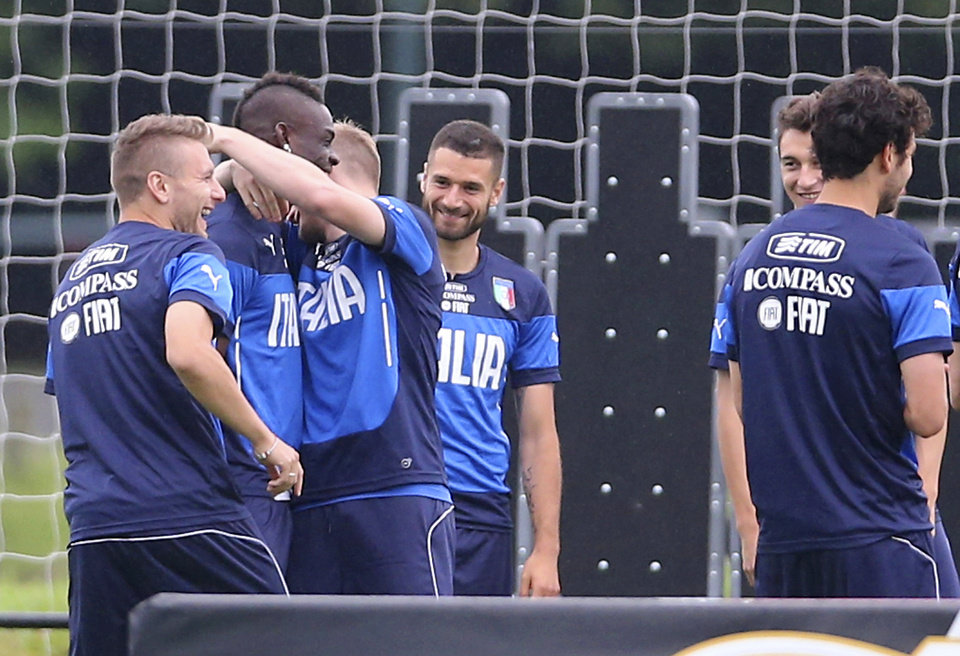 Photo - Italy's Ignazio Abate embraces Mario Balotelli during a training session in Mangaratiba, Brazil, Tuesday, June 10, 2014. Balotelli took care of some personal business before the World Cup training session, proposing to his Belgian girlfriend Fanny Neguesha early Tuesday morning. Italy's squad applauded Balotelli and he responded with a wave of his hand and a wide smile. Then teammates Antonio Candreva, center left, Ciro Immobile, left, and Abate went over to offer a congratulatory hug. (AP Photo/Antonio Calanni)